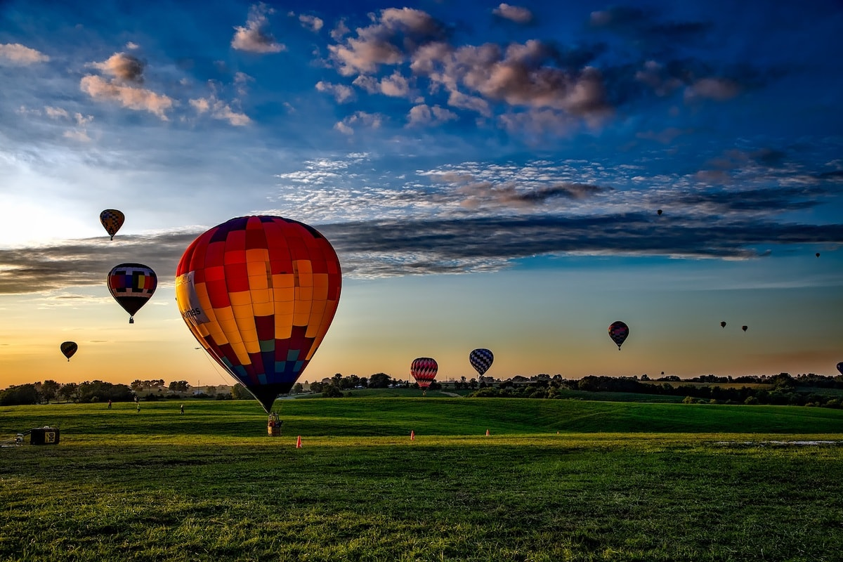 hot air balloons taking off at sunrise